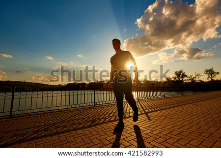 Athletic man after jogging in the rays of the evening sun. Sports concept. - stock photo
