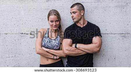Athletic man and woman couple portrait against concrete background. - stock photo