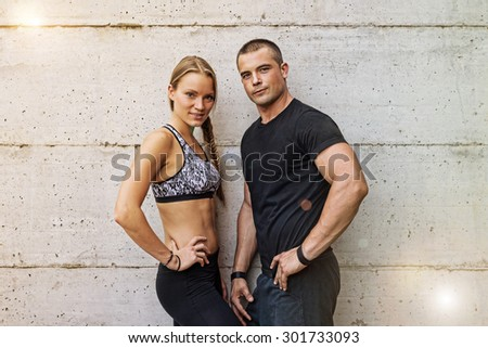 Athletic man and woman couple portrait against concrete background. Concept of happy couple enjoying fitness and healthy lifestyle - Vintage filtered look. - stock photo