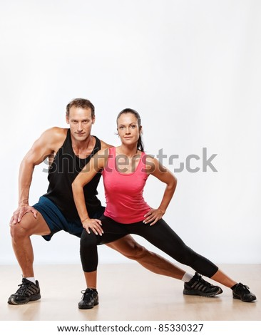 Athletic man and woman doing fitness exercise - stock photo