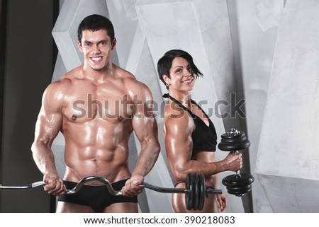 Athletic man and woman with a dumbells. Bodybuilders. - stock photo