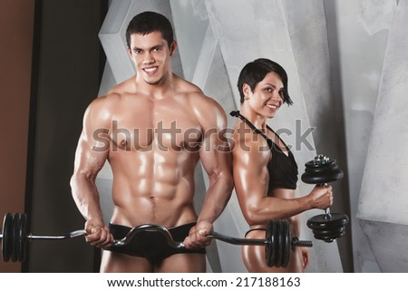 Athletic man and woman with a dumbells. Male and female bodybuilders. Fitness, sport, training, gym and lifestyle concept - two smiling people standing in the gym. The idea of article about sport - stock photo