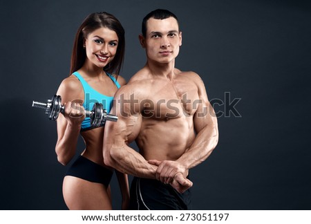 Athletic man and woman with a dumbells on dark background - stock photo