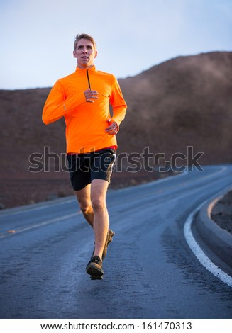 Athletic man jogging outside, training outdoors. Running on road at sunset - stock photo
