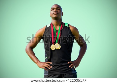 Athletic man posing with his medals against green background - stock photo