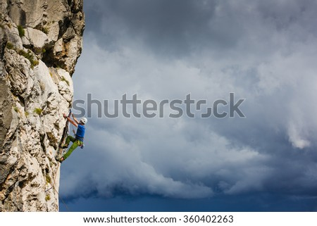 Athletic man rock climbing on the wall - stock photo