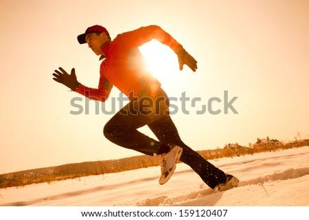 Athletic  man running in winter morning - stock photo