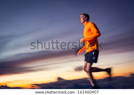 Athletic man running jogging outside, training outdoors. Running at sunset dusk with motion blur - stock photo