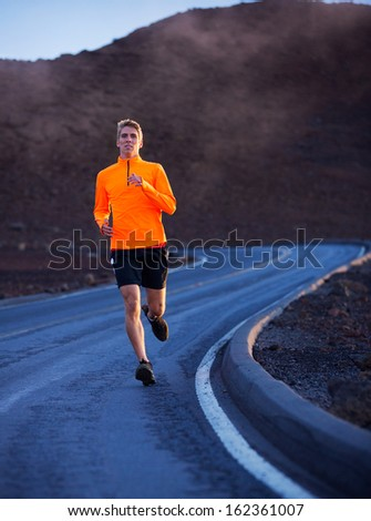 Athletic man running outside, training outdoors. Jogging on road  - stock photo