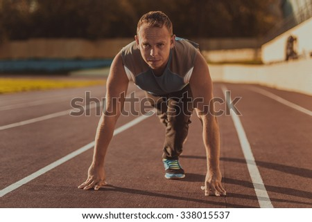 Athletic man standing in a posture ready to run on a treadmill. - stock photo