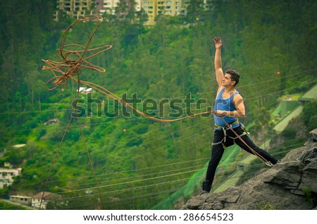 athletic man standing on cliff throwing rope with right arm down mountain - stock photo