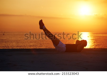 Athletic man training abdominal, fitness man exercising sit up lying on the beach, silhouette of healthy man with muscular body doing some exercises for the abs, fitness and healthy lifestyle concept - stock photo