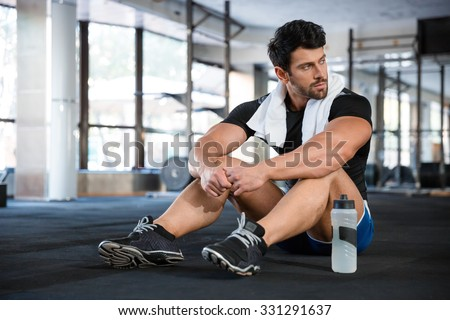 Athletic man wearing blue shorts and black t-shirt sitting on the floor in gym - stock photo