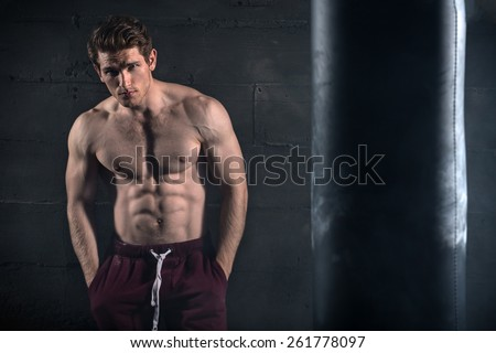 Athletic man with naked torso near concrete wall - stock photo