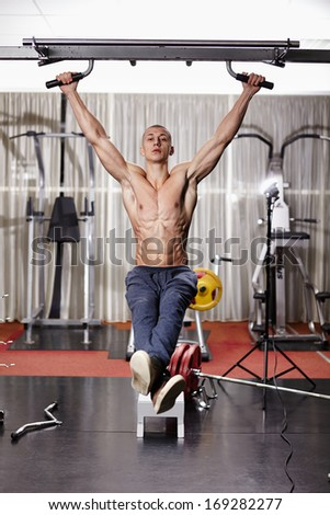 Athletic man working his abs by doing the hanging legs raise at the gym - stock photo