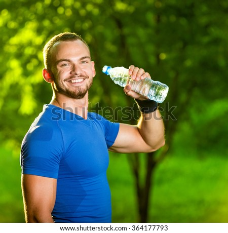 Athletic mature man drinking water from a bottle - stock photo