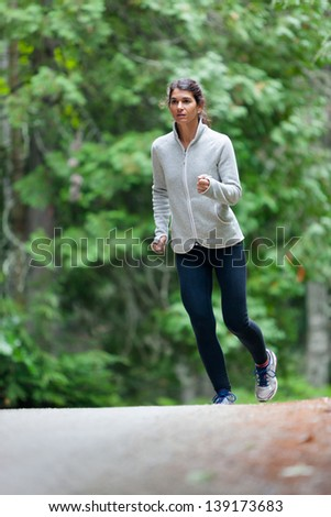 Athletic middle aged caucasian woman on a run in green leaved woods on a dirt road in Surry, Maine, USA wearing black tights and grey fleece jacket. - stock photo