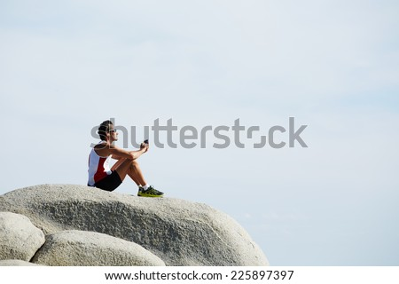 Athletic runner enjoying amazing sunny day while after workout outdoors, man resting after intensive fitness training, fit man enjoying the sun listen the music, freedom concept,  - stock photo