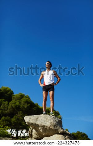 Athletic runner with muscular body enjoying amazing sunny day while doing workout outdoors, man resting after intensive fitness training outdoors - stock photo