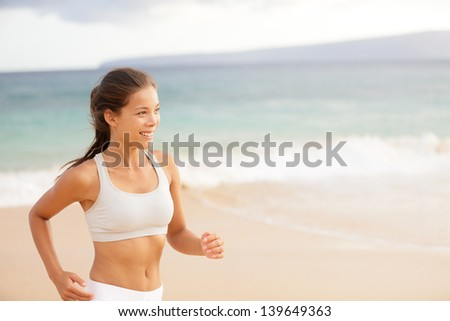 Athletic running happy young woman in sportswear jogging on beach by the ocean training to maintain her fitness. Young female sport model of mixed Asian and Caucasian ethnicity in her twenties. - stock photo