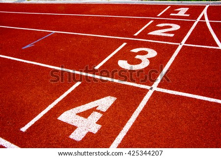 Athletic running track in weathered red rubber with numbered lan - stock photo