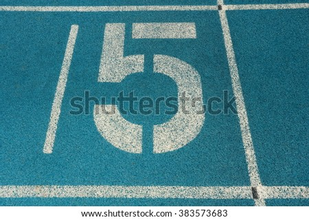 Athletic running track with number five - stock photo