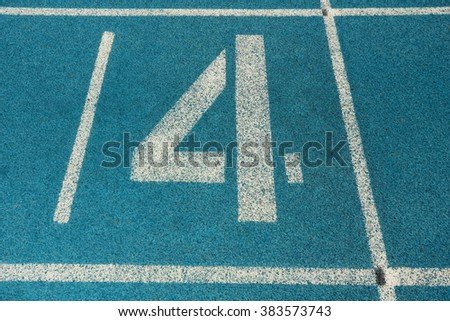Athletic running track with number four - stock photo