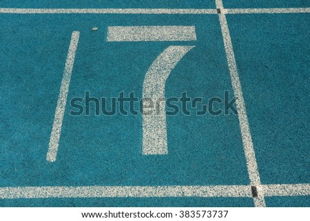 Athletic running track with number seven - stock photo