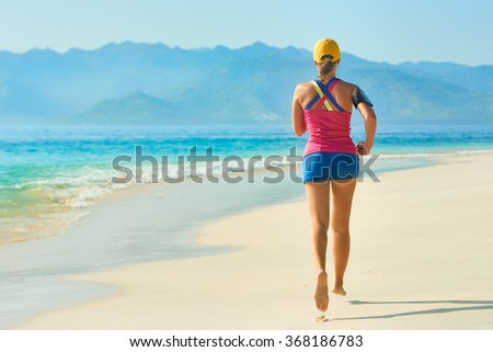 Athletic running woman. Woman runner jogging during outdoor workout on beach. Fitness concept. - stock photo