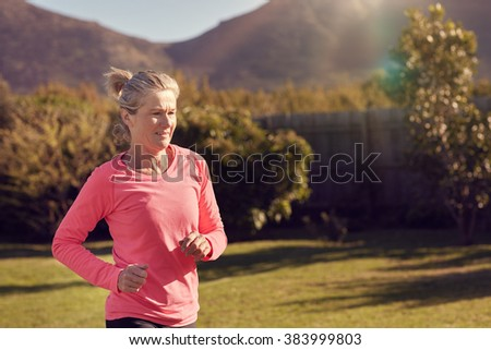 Athletic senior woman in a pink sportswear top, training by doing some jogging outdoors with grass and trees, on a sunlit morning  - stock photo