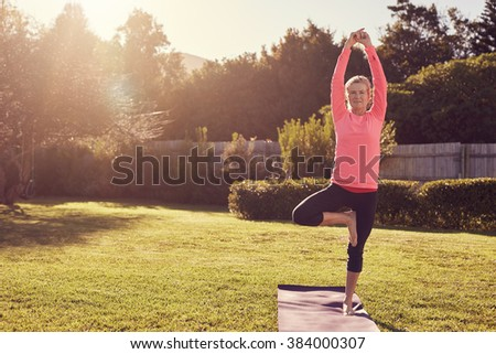 Athletic senior woman standing confidently in a balancing pose on her yoga mat, in her garden on the grass, with morning summer sunflare filtering through the trees - stock photo