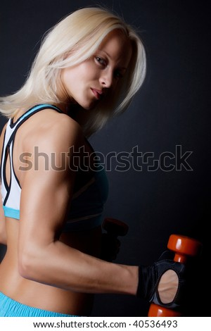 Athletic sexy blond woman doing exercise in gym room - stock photo