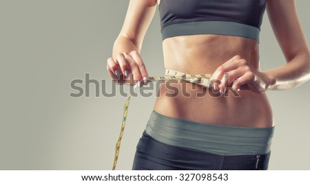 Athletic slim woman measuring her waist by measure tape after a diet over gray gray background. High resolution  - stock photo