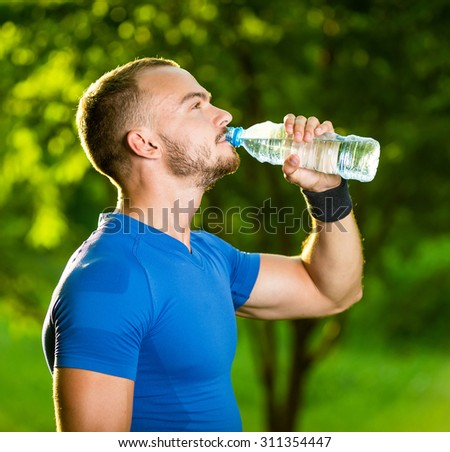 Athletic sport man drinking water from a bottle. Cold drink after outdoor fitness. - stock photo
