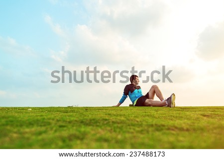 athletic sportsman resting after sport in the park and looking far away at the sunset - stock photo