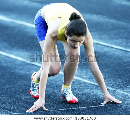 Athletic teenage girl in start position on track . - stock photo