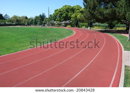 Athletic Track Curving Around Green Grass Field - stock photo