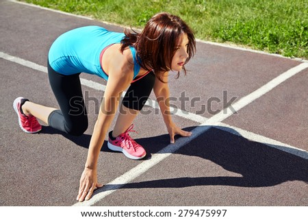 athletic woman at the starting line athlete running on jogging track at the stadium. jogging outdoors - stock photo