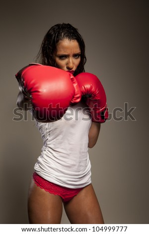 Athletic woman boxer wearing red leather boxing gloves wet with perspiration throwing a punch at the camera - stock photo
