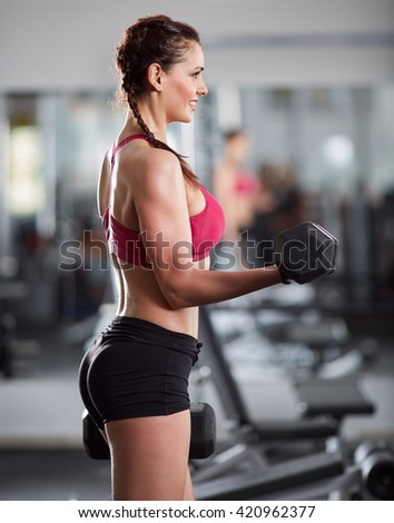 Athletic woman doing biceps curl with dumbbells in the gym - stock photo