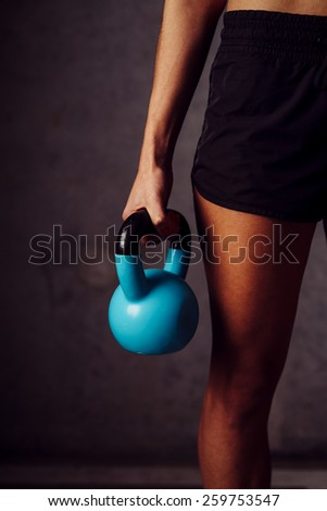 Athletic woman holding a kettlebell - stock photo