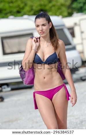 Athletic woman in caravan parking. She is wearing two pieces swimwear and holding her bag at the shoulder. Many caravans as background. Vertical picture - stock photo