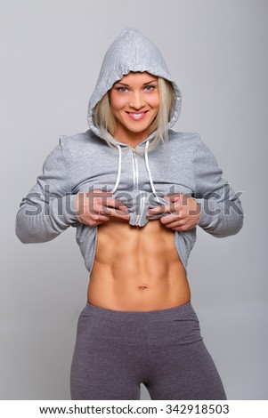 Athletic woman in grey hoodie showing her muscular stomach. - stock photo