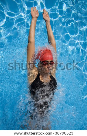 Athletic woman in swimming gear with blue swimming pool - stock photo