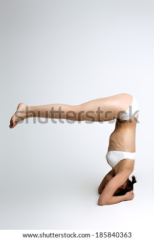 Athletic woman in white balance on hands - stock photo