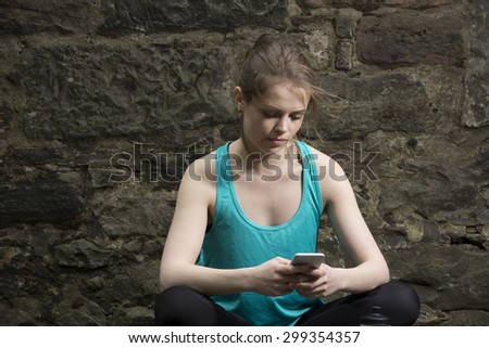 Athletic woman looking at Smart Phone after training. Action and healthy lifestyle concept. - stock photo