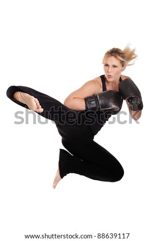 Athletic woman performing a flying side kick isolated on a white background - stock photo