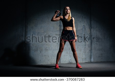 Athletic woman posing with kettlebell against concret wall - stock photo