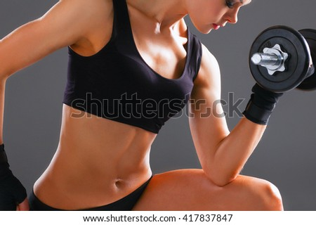 Athletic woman pumping up muscules with dumbbells - stock photo