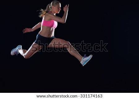 Athletic woman running on athletics race  track - stock photo
